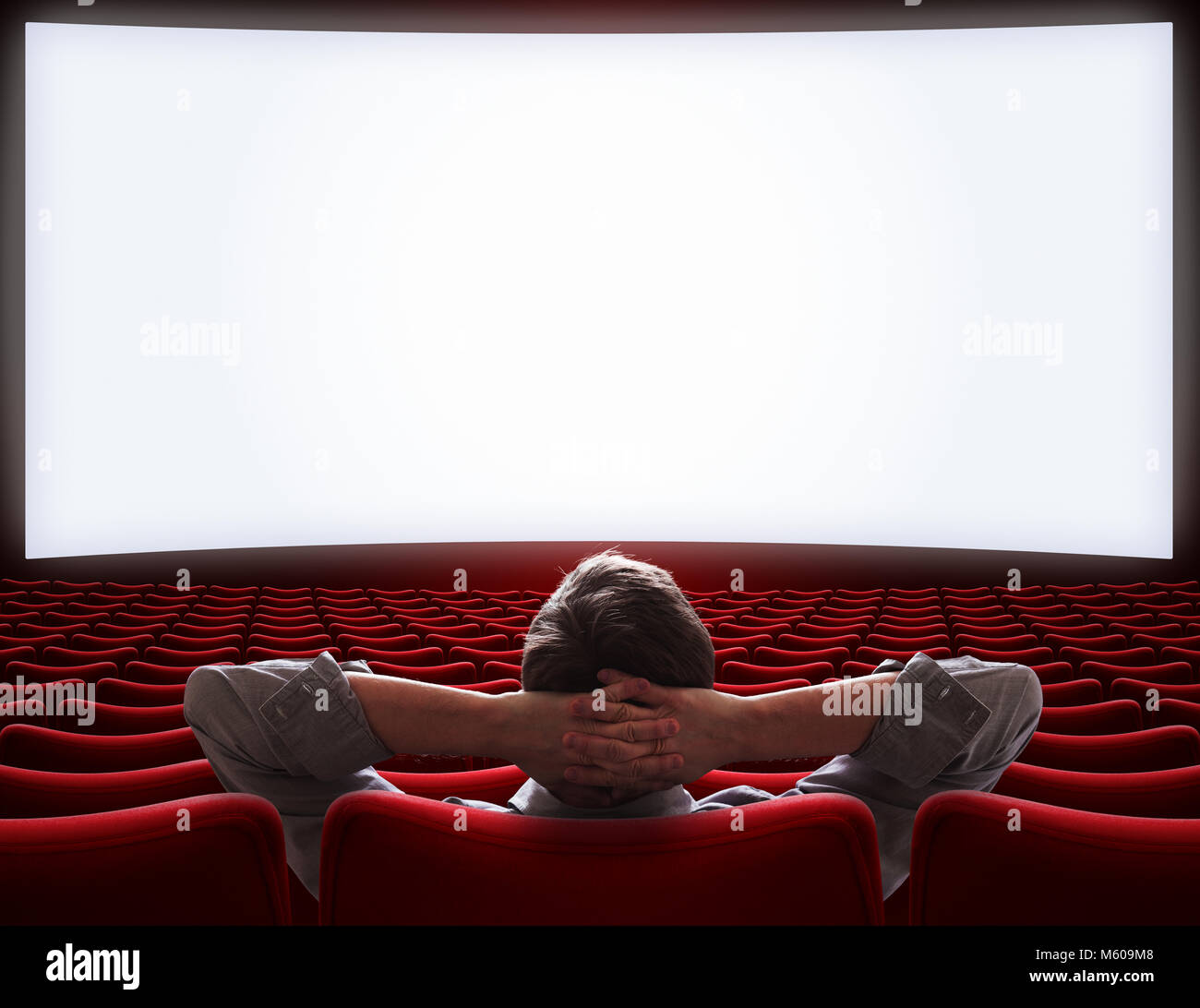 empty movie theater hall with lonely VIP man sitting - Stock Image