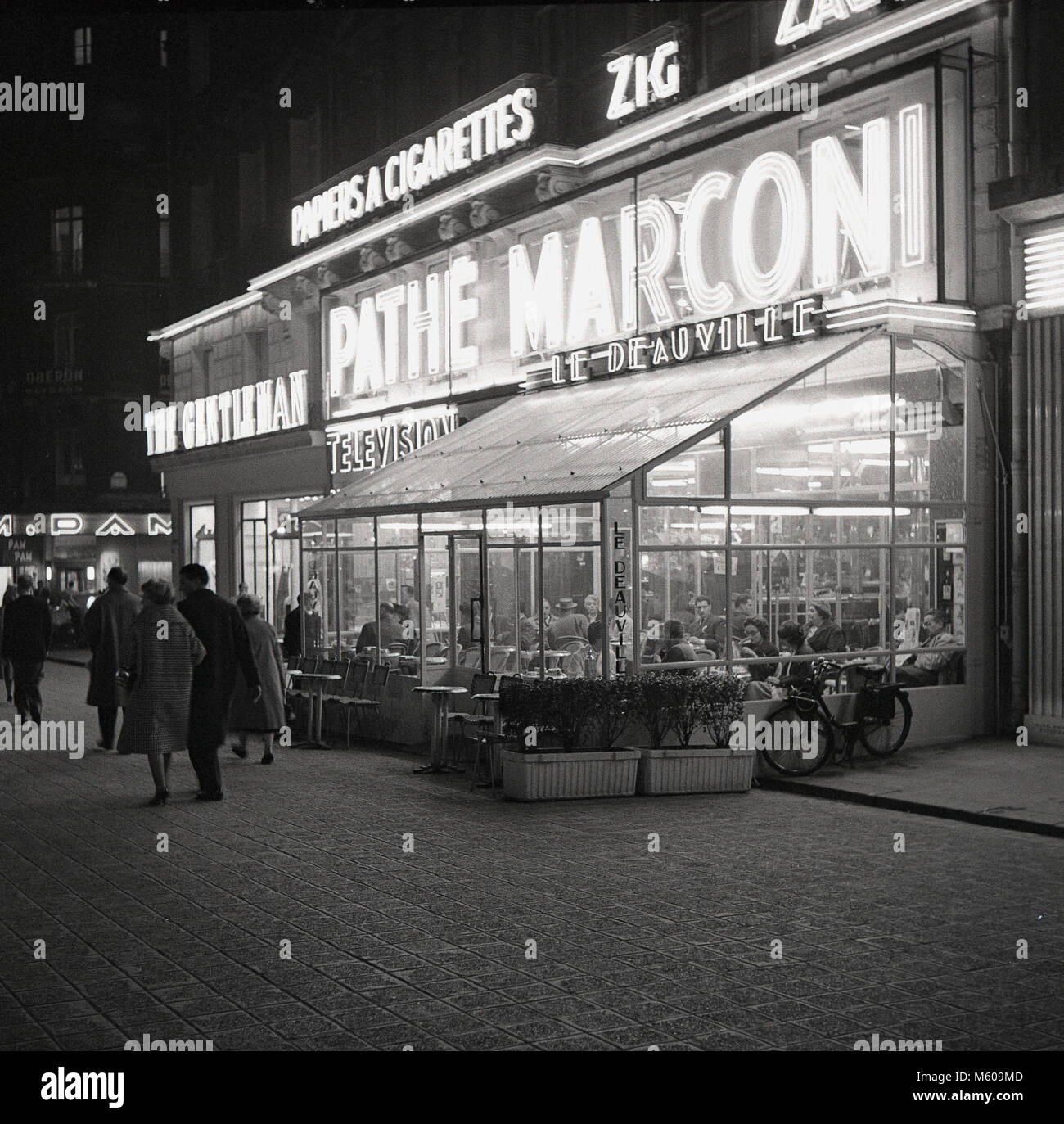 1950s, historical picture of Paris in the evening outside cafe Le Deauville, 75 Avenue des Champs Elysees, with - Stock Image