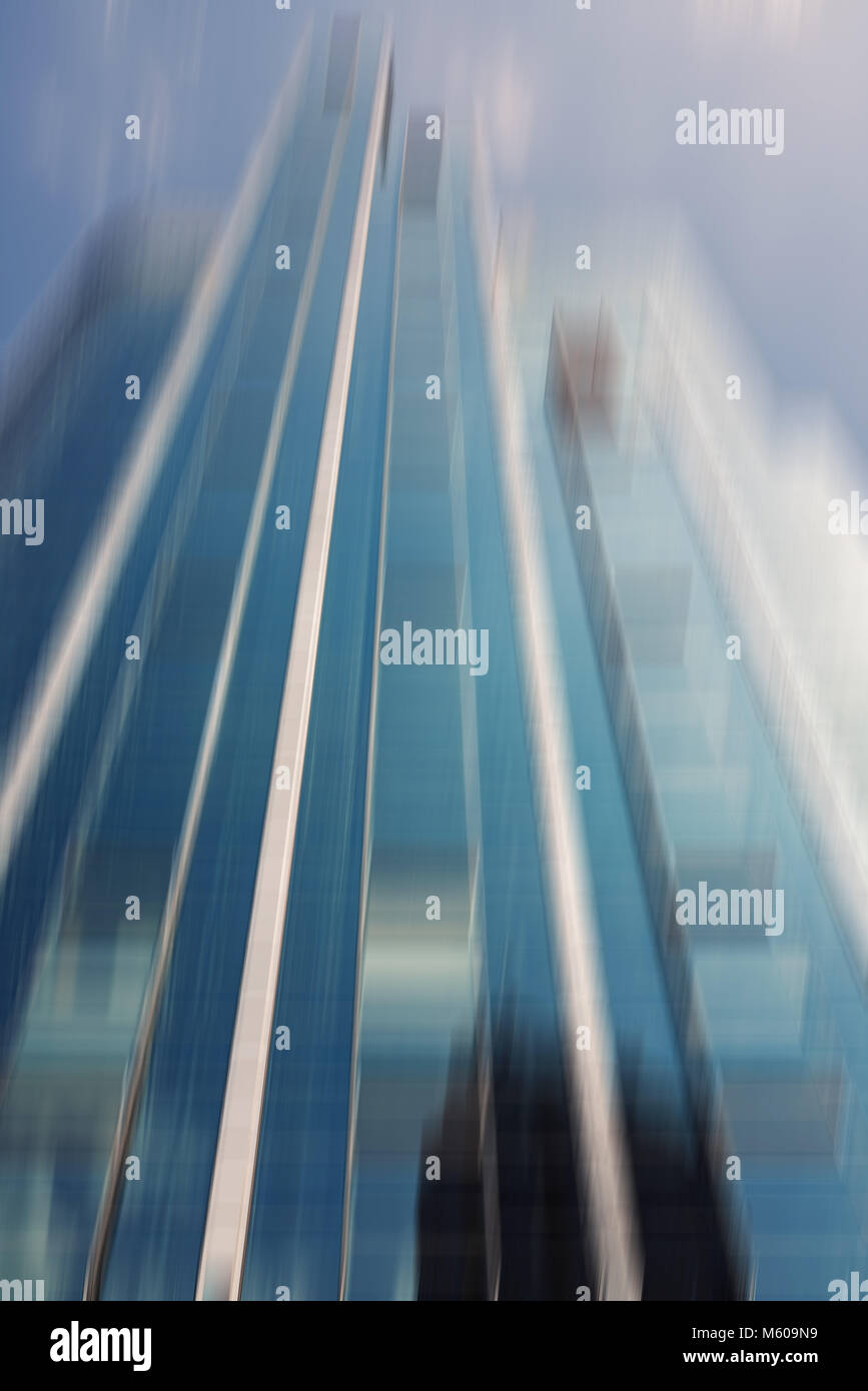 Defocused glass skyscraper in the commercial district of a city - Stock Image