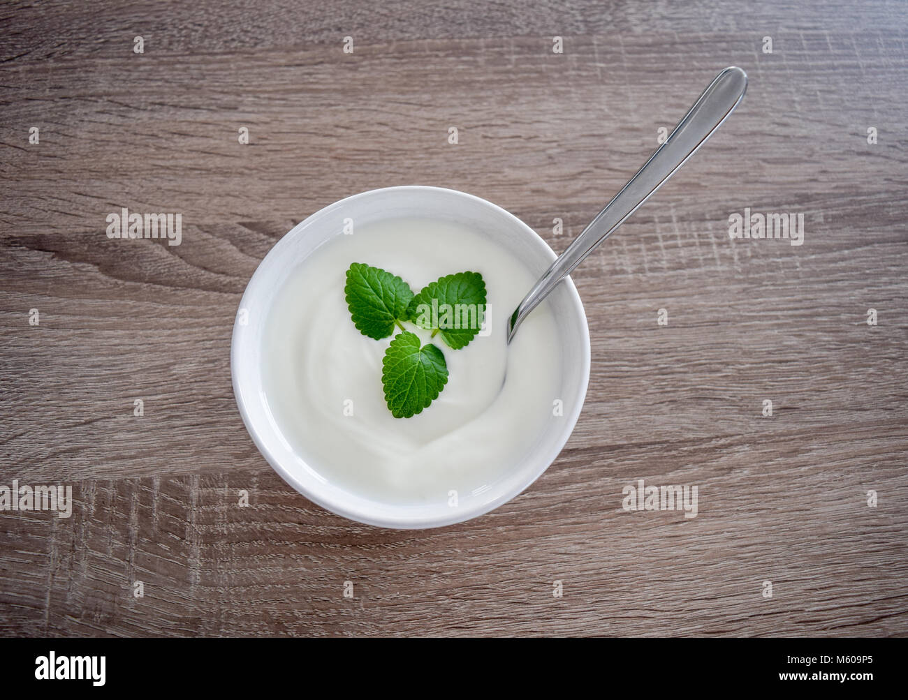 Ceramic bowl of white yogurt with mint leaves as decoration and spoon inside isolated on vintage rustic wooden table - Stock Image
