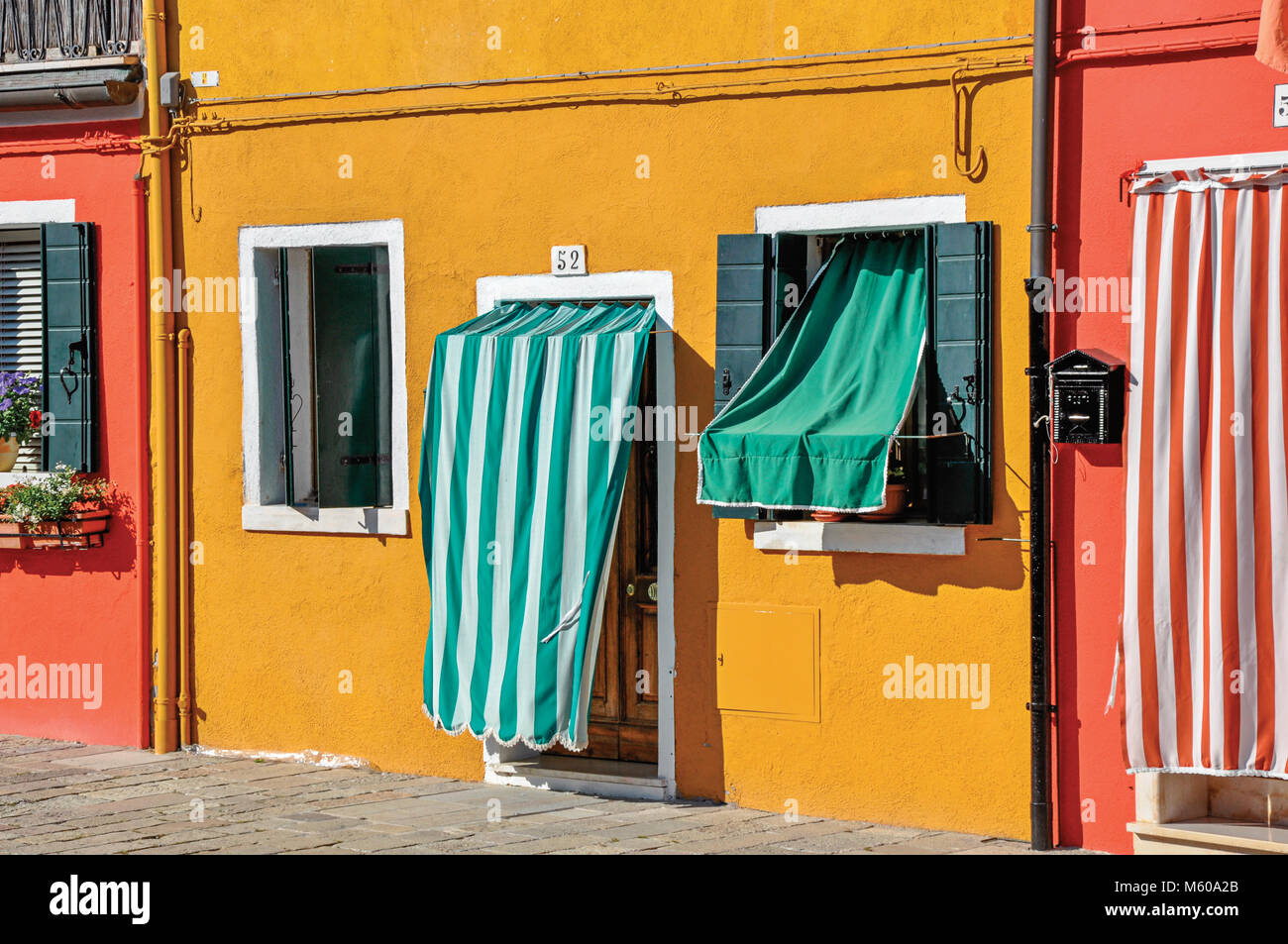 Close-up of colorful houses and doors with cloth on a sunny day in Burano a gracious little town full of canals near Venice. & Burano Italy. Close-up of colorful houses and doors with cloth on a ...