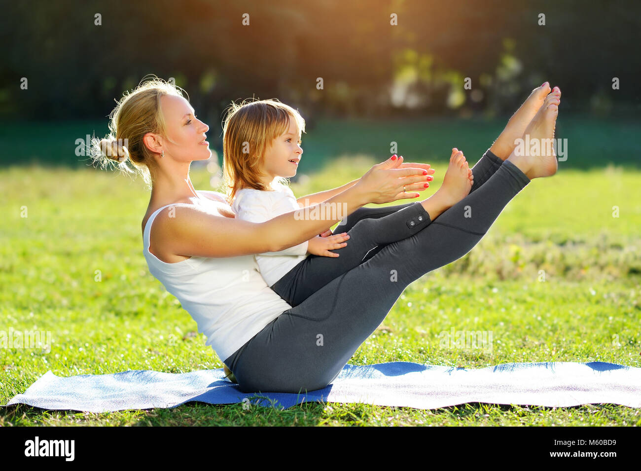 Beautiful woman practicing sitting boat yoga pose with her little daughter outdoor Stock Photo