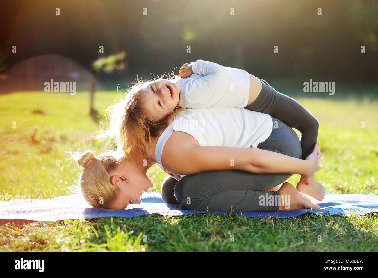 Happy little girl playing with her mom practicing child yoga pose Stock Photo