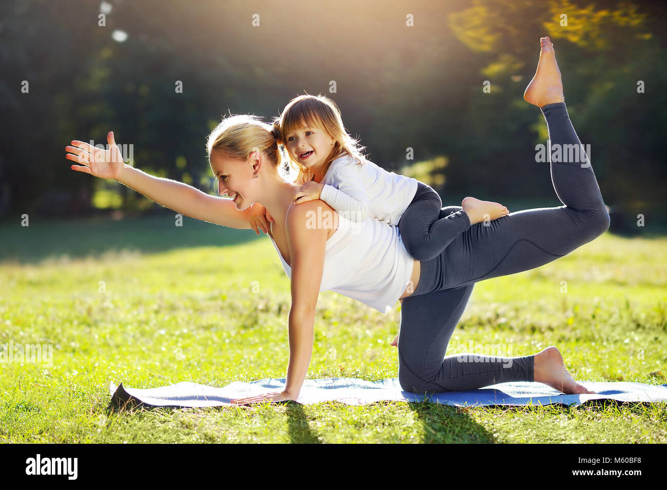 Little girl is playing with her sportive mother practicing yoga cat pose together - Stock Image