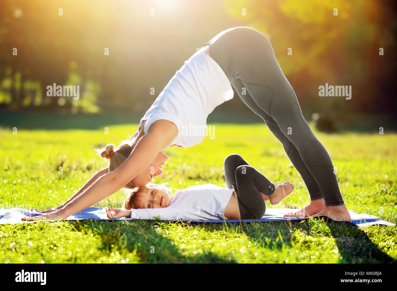 Mother practicing Downward Facing Dog yoga  Pose playing with her daughter laying on the mat Stock Photo