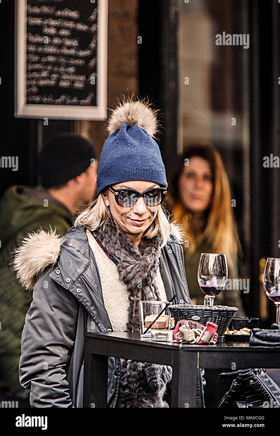 Biarritz, France-February 24,2018: Stylish French woman enjoys the aperitif on an outdoor terrace in the streets - Stock Image