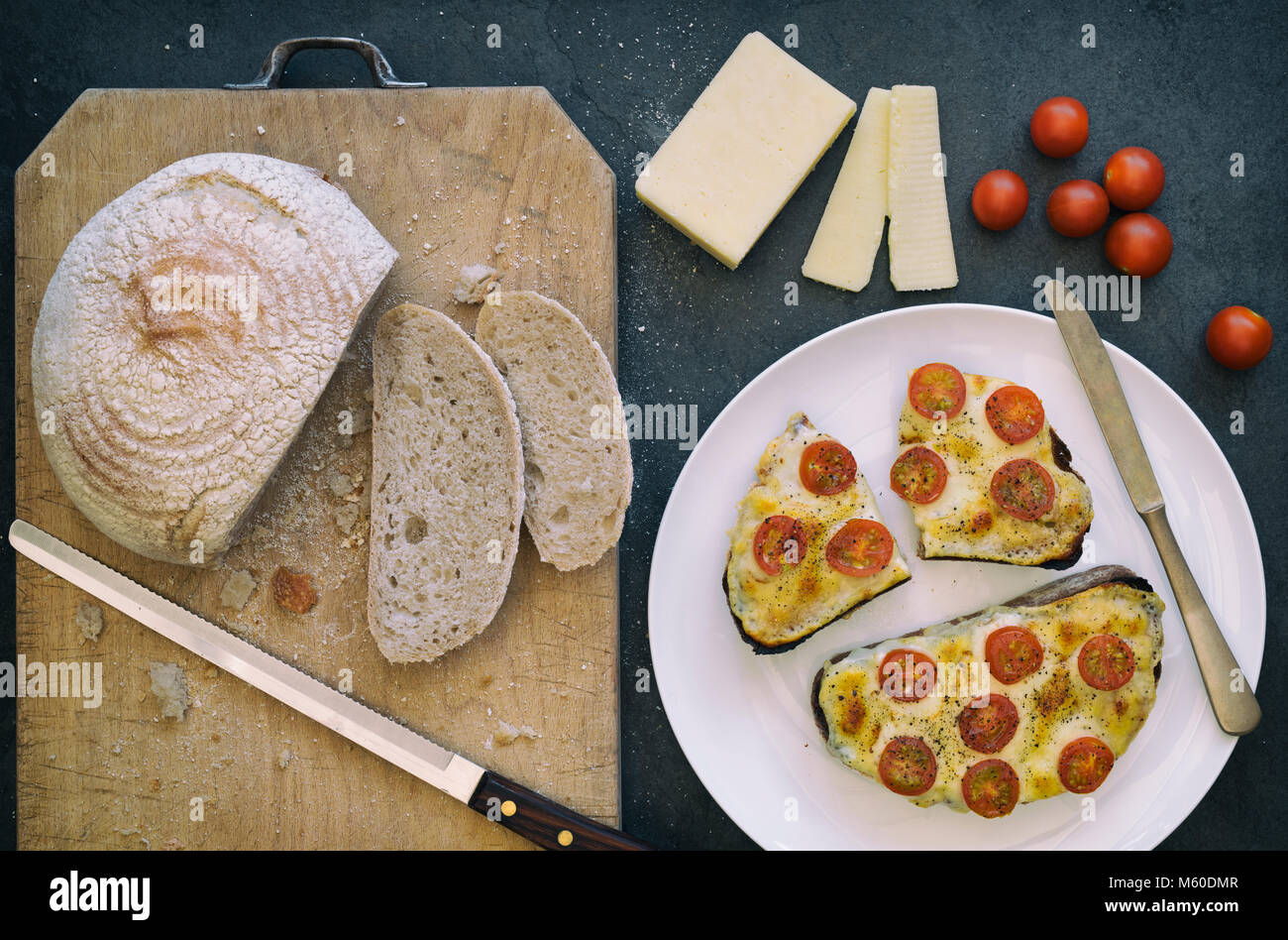 Cheese on toast. Cheese and tomatoes on toasted rye bread with a slate background Stock Photo