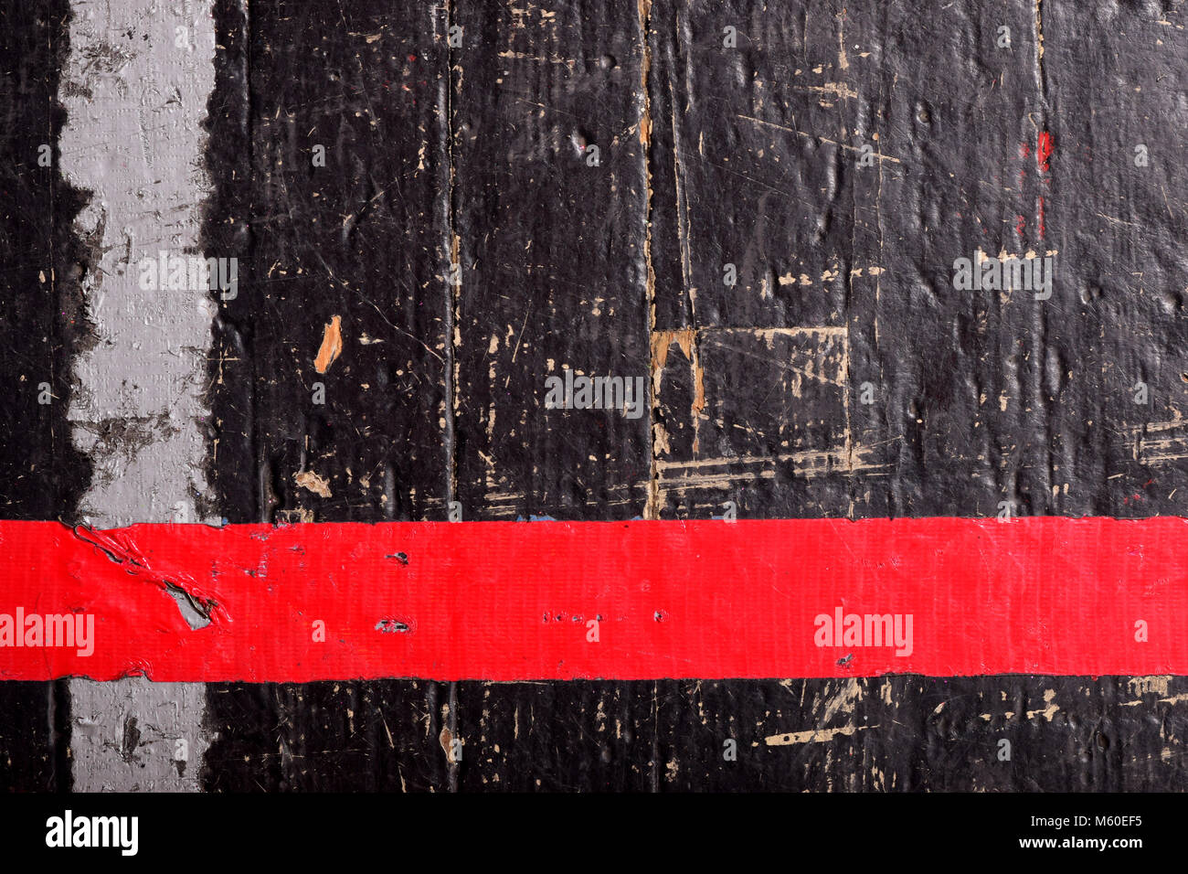 Scuffed wooden gym floor with peeling tape. - Stock Image