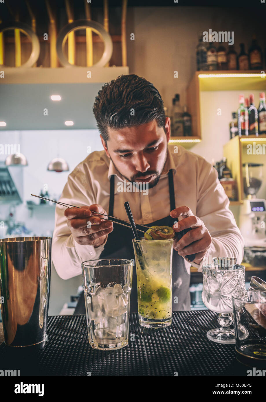 Bartender decorating cocktail with kiwi - Stock Image