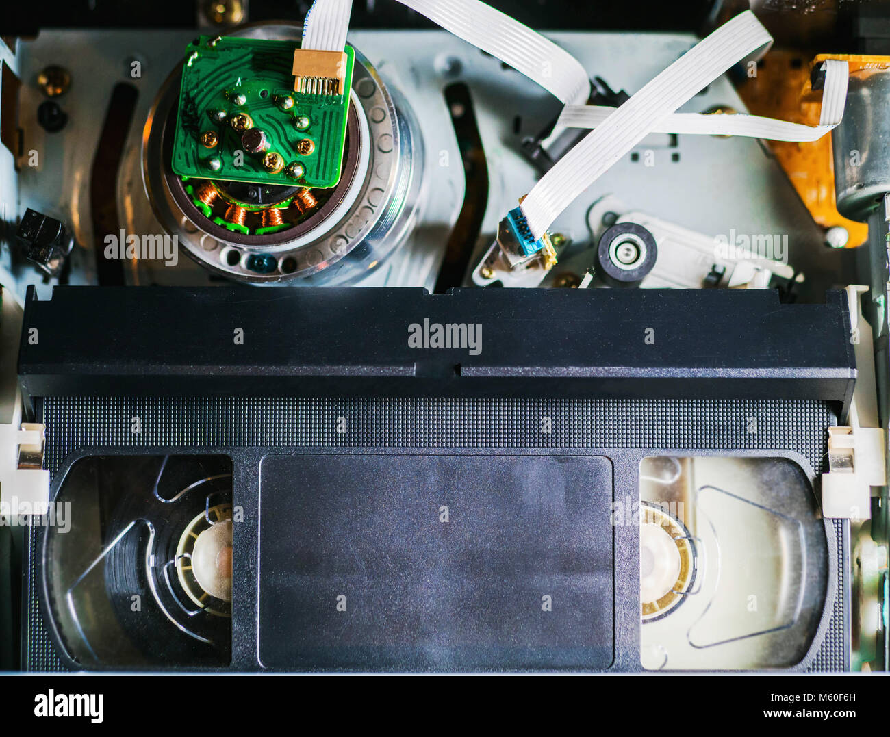 VHS tape inside a VCR player, reels moving while reading the contents. Close-up detail shot. Stock Photo
