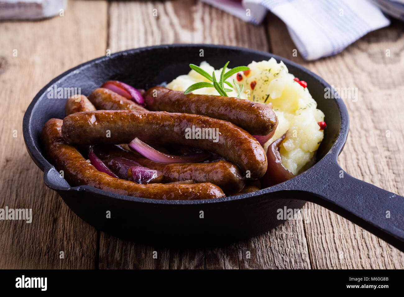 Sausage and onion casserole served with potato mash in cast iron skillet on rustic wooden table Stock Photo