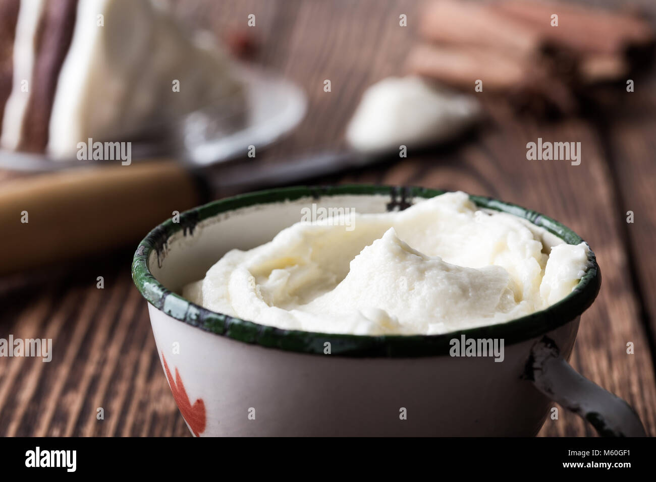Homemade cream cheese frosting in rural mug on rustic wooden table ready to use - Stock Image