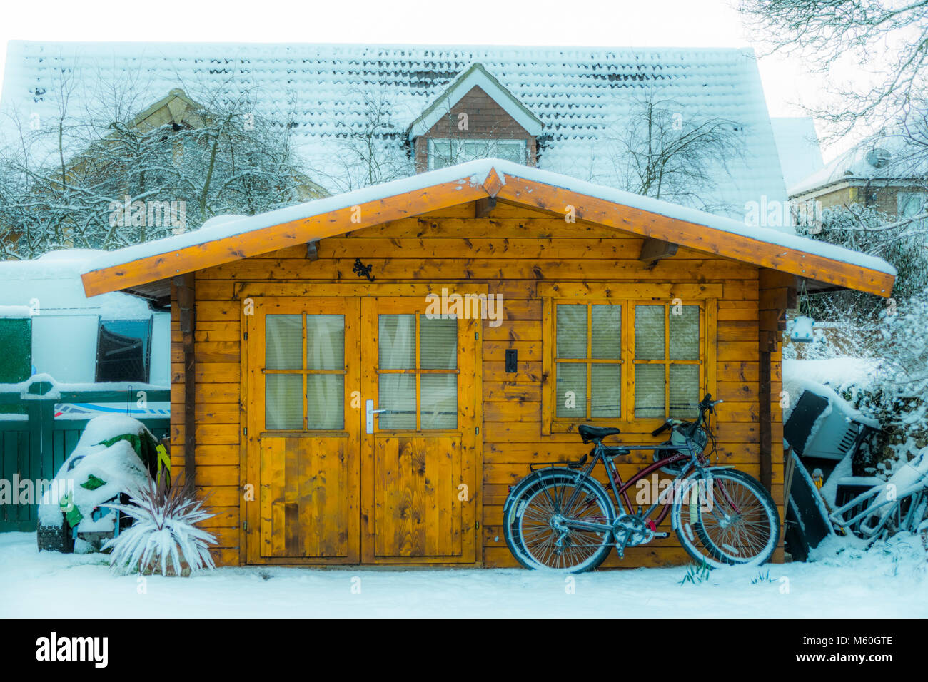 Fresh early morning winter snow around a log cabin / summerhouse (wooden garden building), in a snowy village garden. - Stock Image