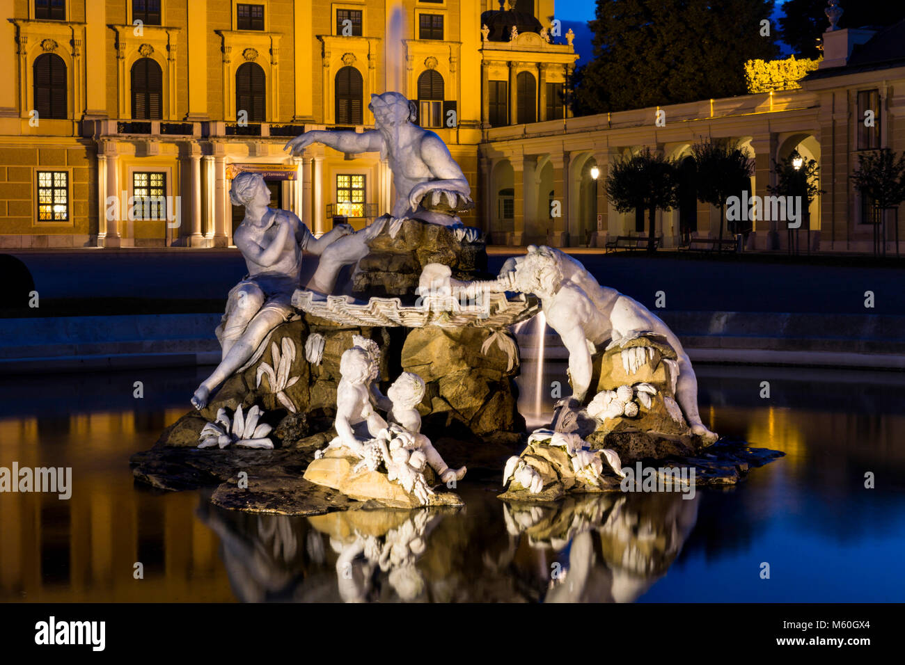 Schönbrunn Palace and one of the Naiad Fountains (spirits of springs and rivers) illuminated at night, Schonbrunn, - Stock Image