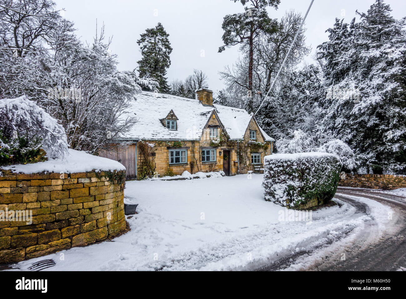 Traditional old Cotswold stone cottage covered in snow - Stock Image