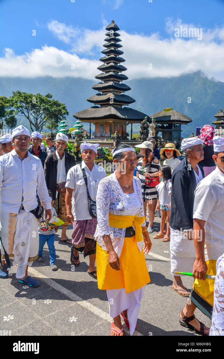 Balinese villagers participating in traditional religious Hindu procession in Ulun Danu temple Beratan Lake in Bali Stock Photo