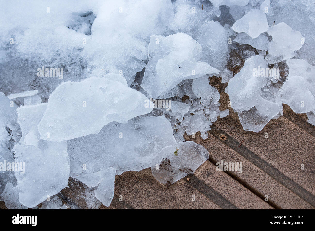 A semi-abstract view of the contrasting colour tones and textures of icy chunks of snow beside a cleared portion - Stock Image