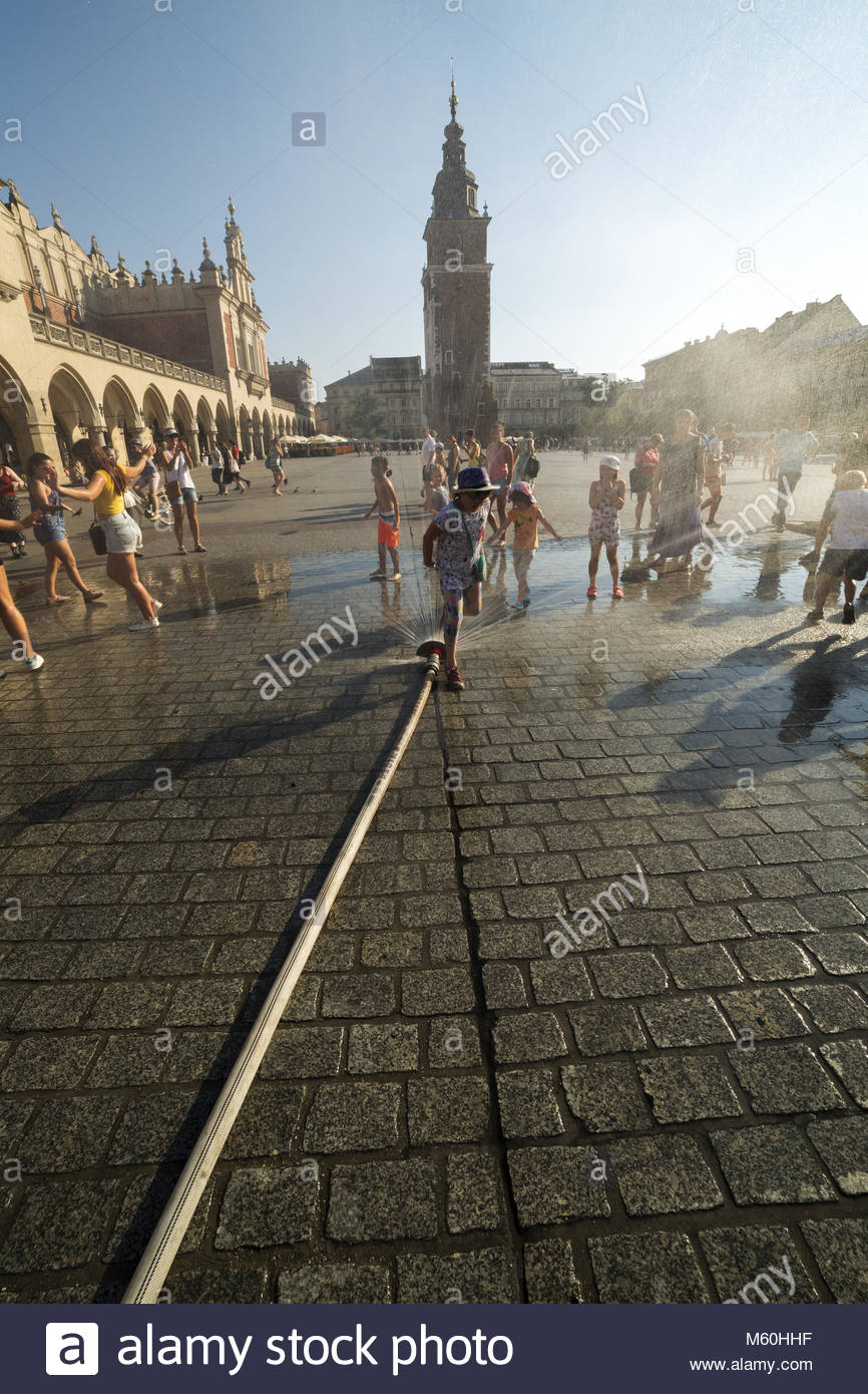 Children play and adults cool down under the mist sprey deployed by the local authority during the heatwave, Rynek - Stock Image