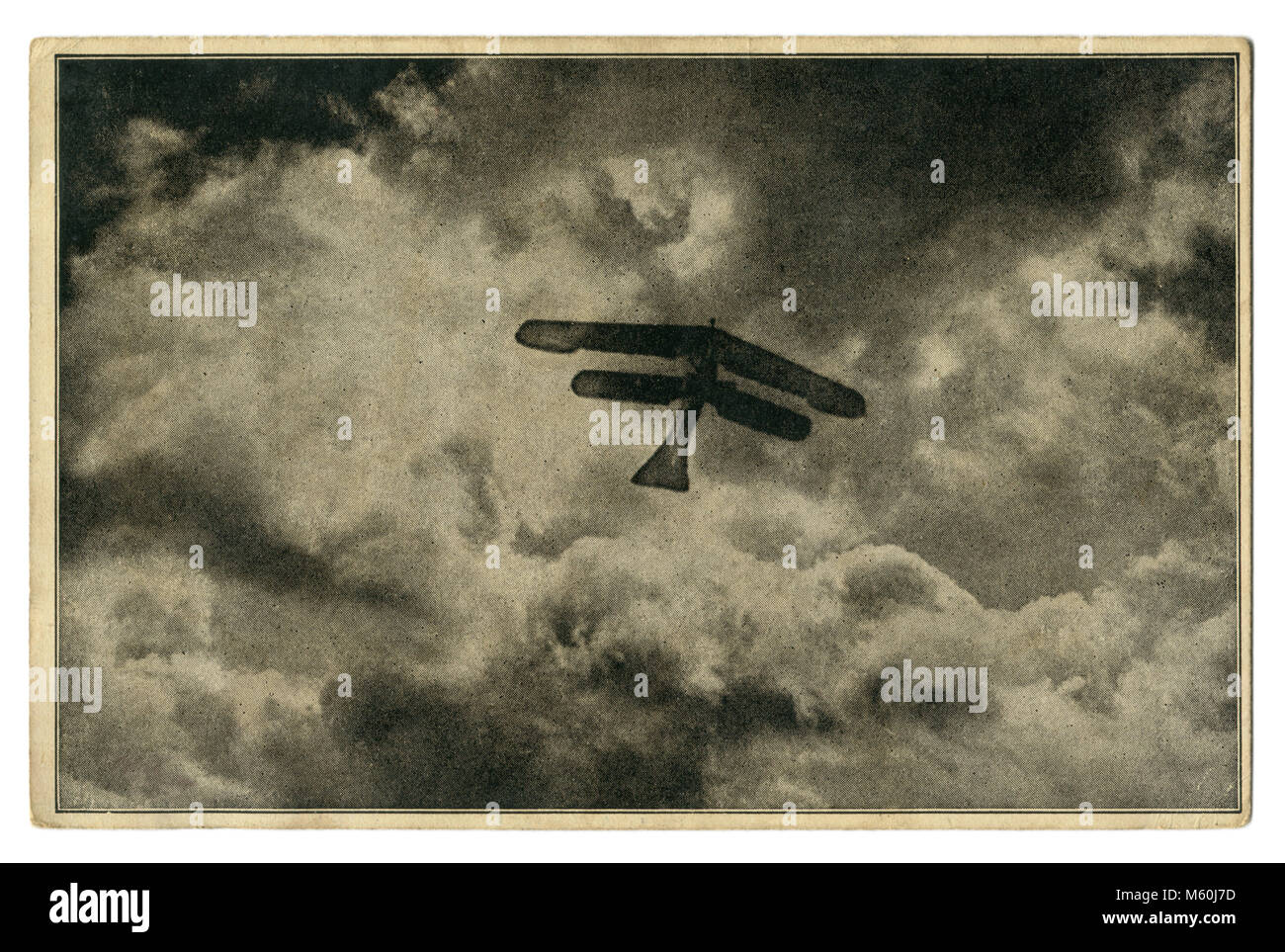 "Old German postcard: ""A high-altitude flight"" Silhouette of a biplane against a background of clouds. The first Stock Photo"
