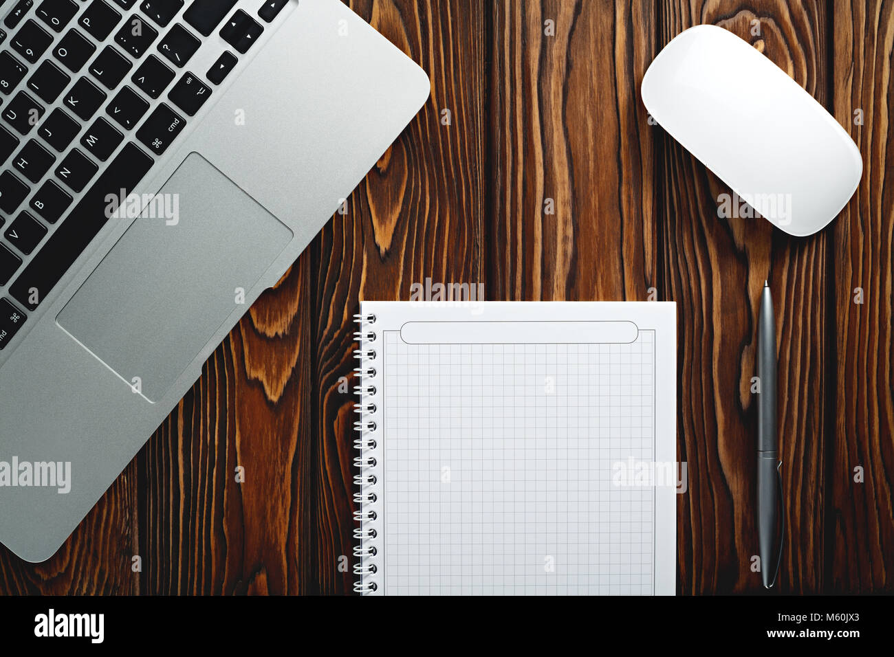 Notepad, laptop,  and pen on wood texture table, start of Morning work office, vintage style. Business concept background Stock Photo