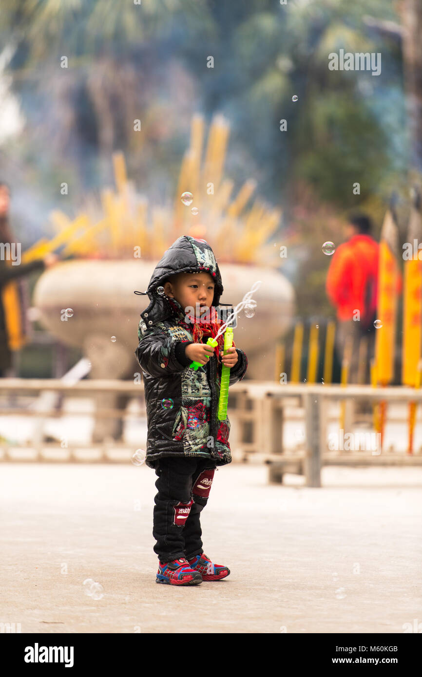 Young boy playing with soap bubbles at a buddhist temple - Stock Image