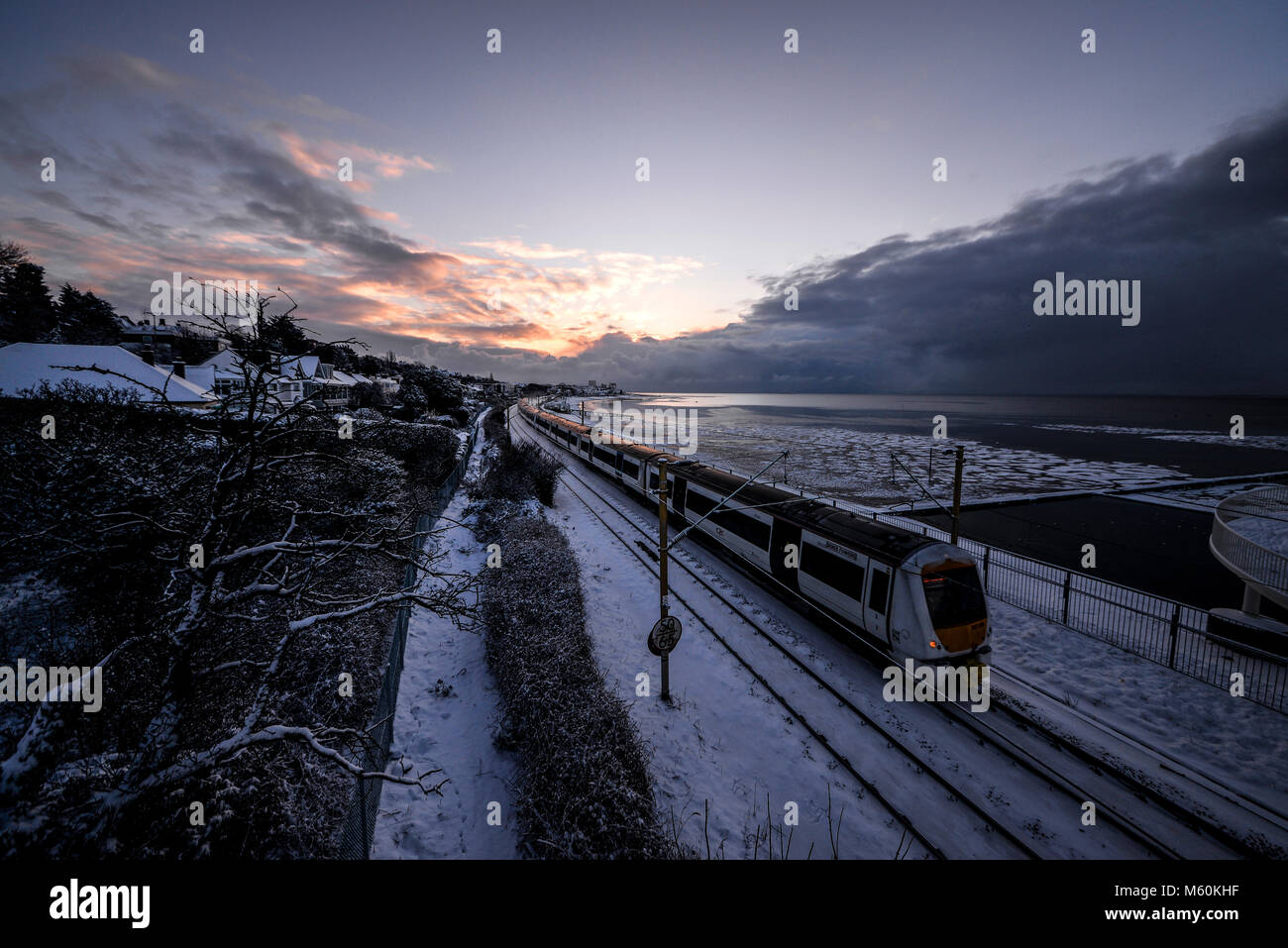 Train in snow. C2C railway train running through snow covered lines in Chalkwell near Southend on Sea, Essex at Stock Photo