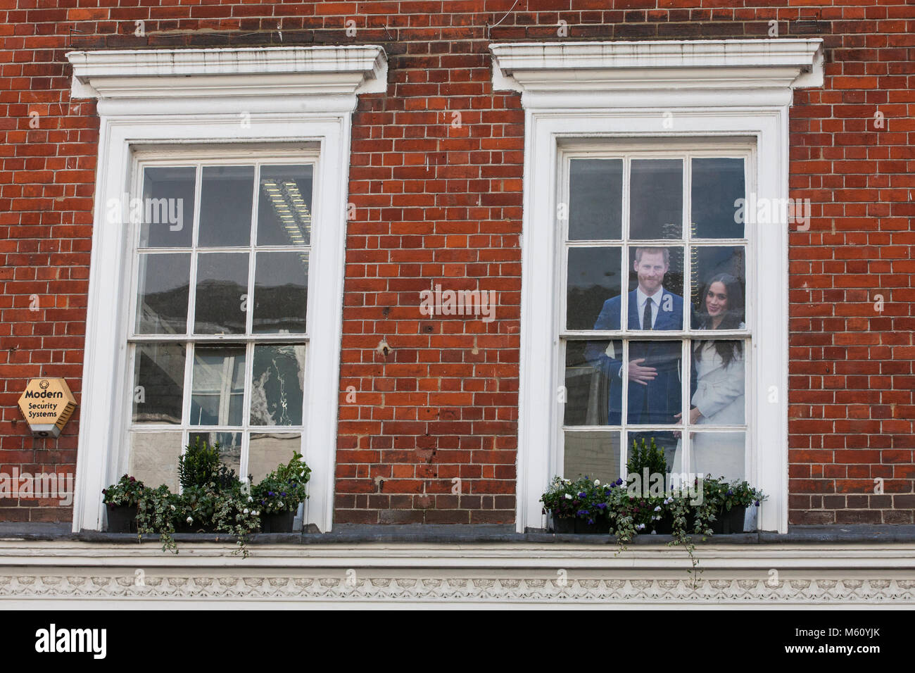 Windsor, UK. 27th February, 2018. Cut outs of Prince Harry and Meghan Markle peer out from a window above Windsor Stock Photo
