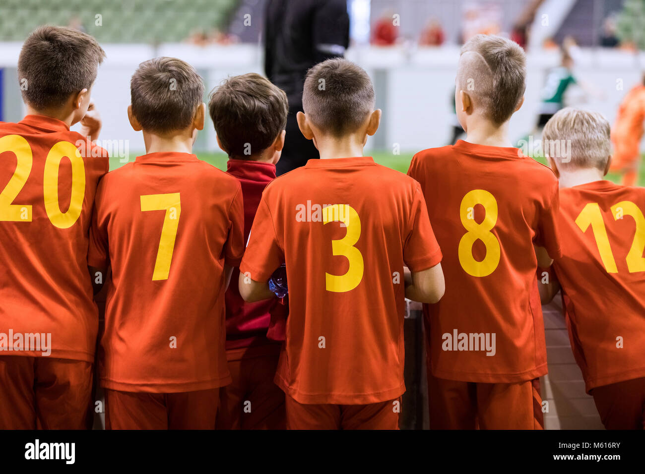 Indoor soccer team. Futsal indoor soccer match for kids. Children supporting teammates. Sports arena in the background. - Stock Image