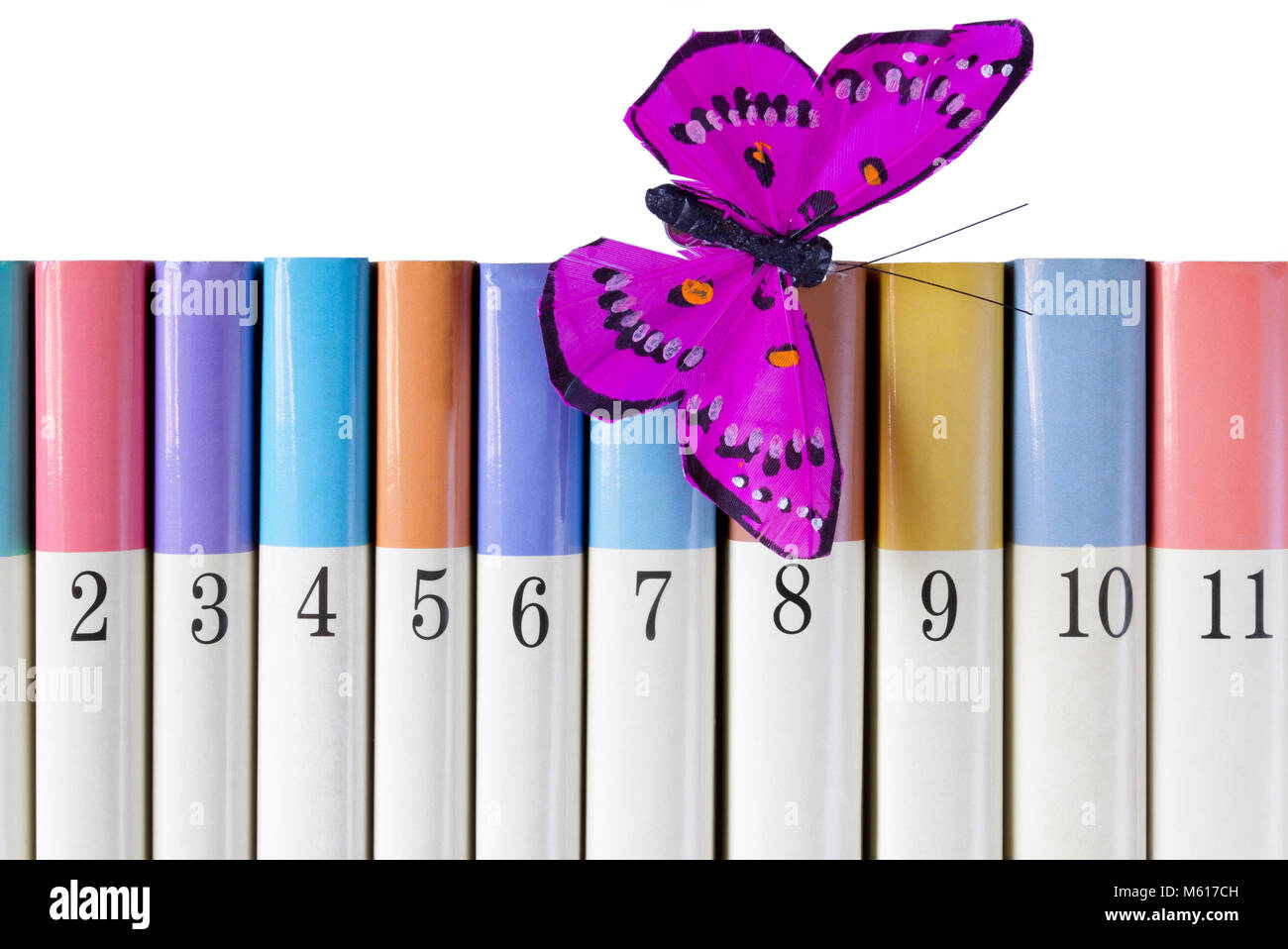 A series of books in different colours and ordered by number, with a silk butterfly alighted on the cover of one - Stock Image