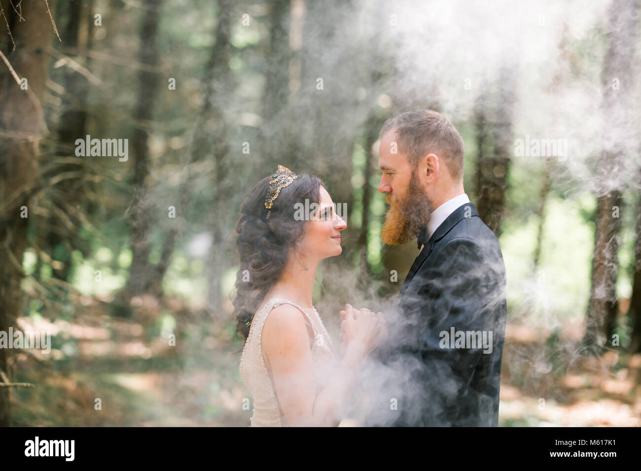 beautiful couple standing on the background of pine forest - Stock Image
