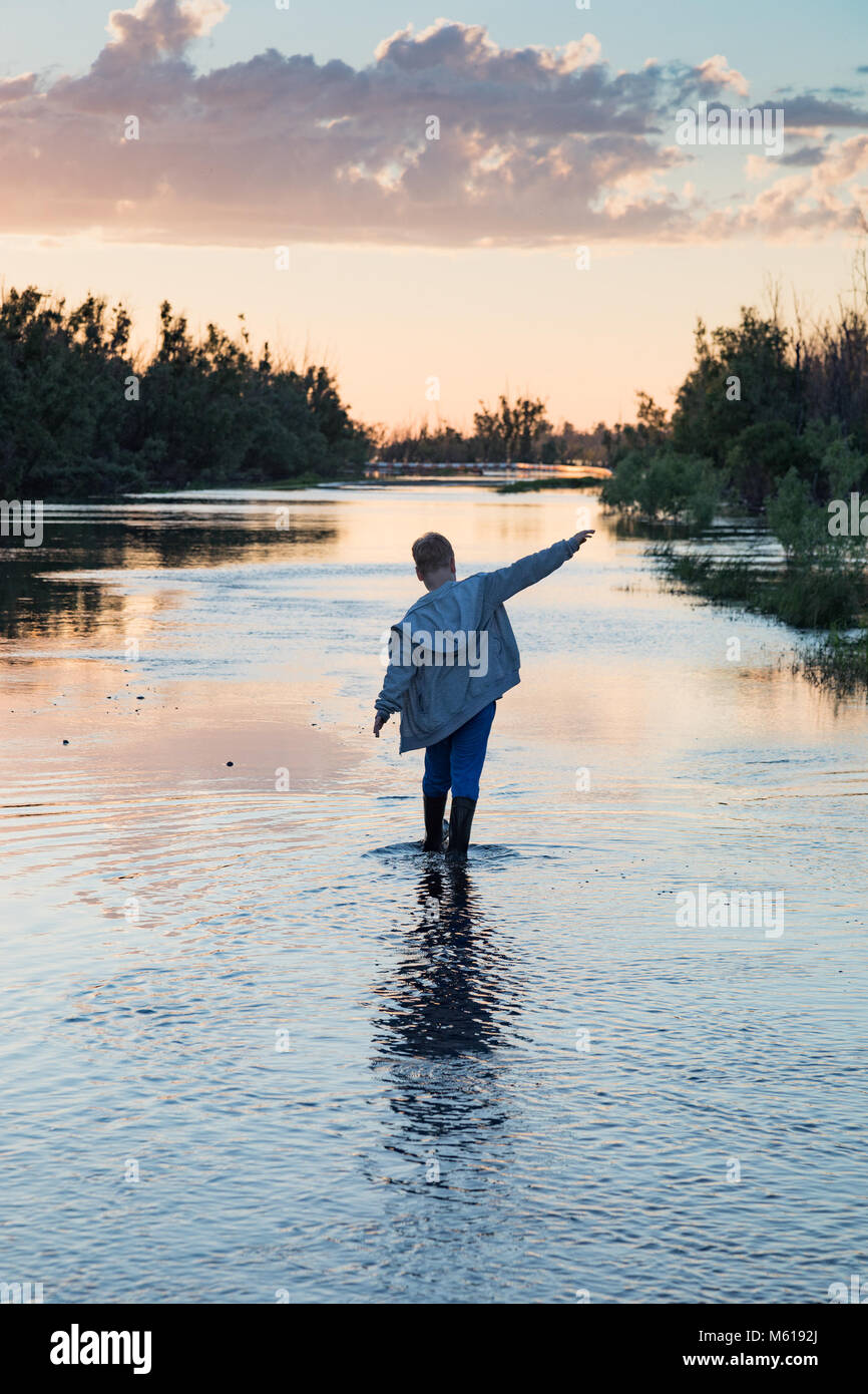 Boy on the submerged rural road - Stock Image