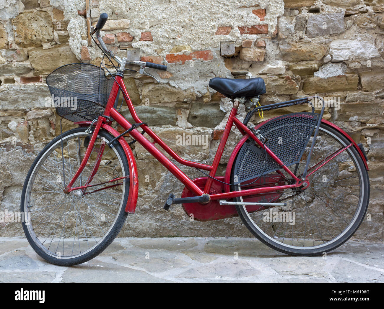 Red women's bicycle against a brick wall - Stock Image