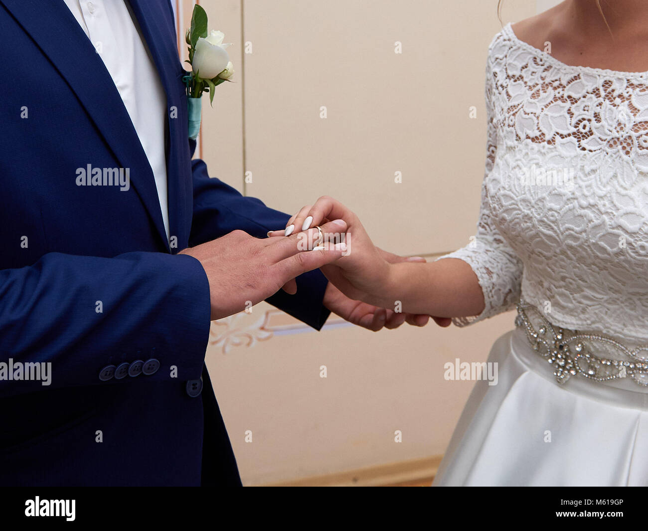 Bride and groom holding hands close up - Stock Image