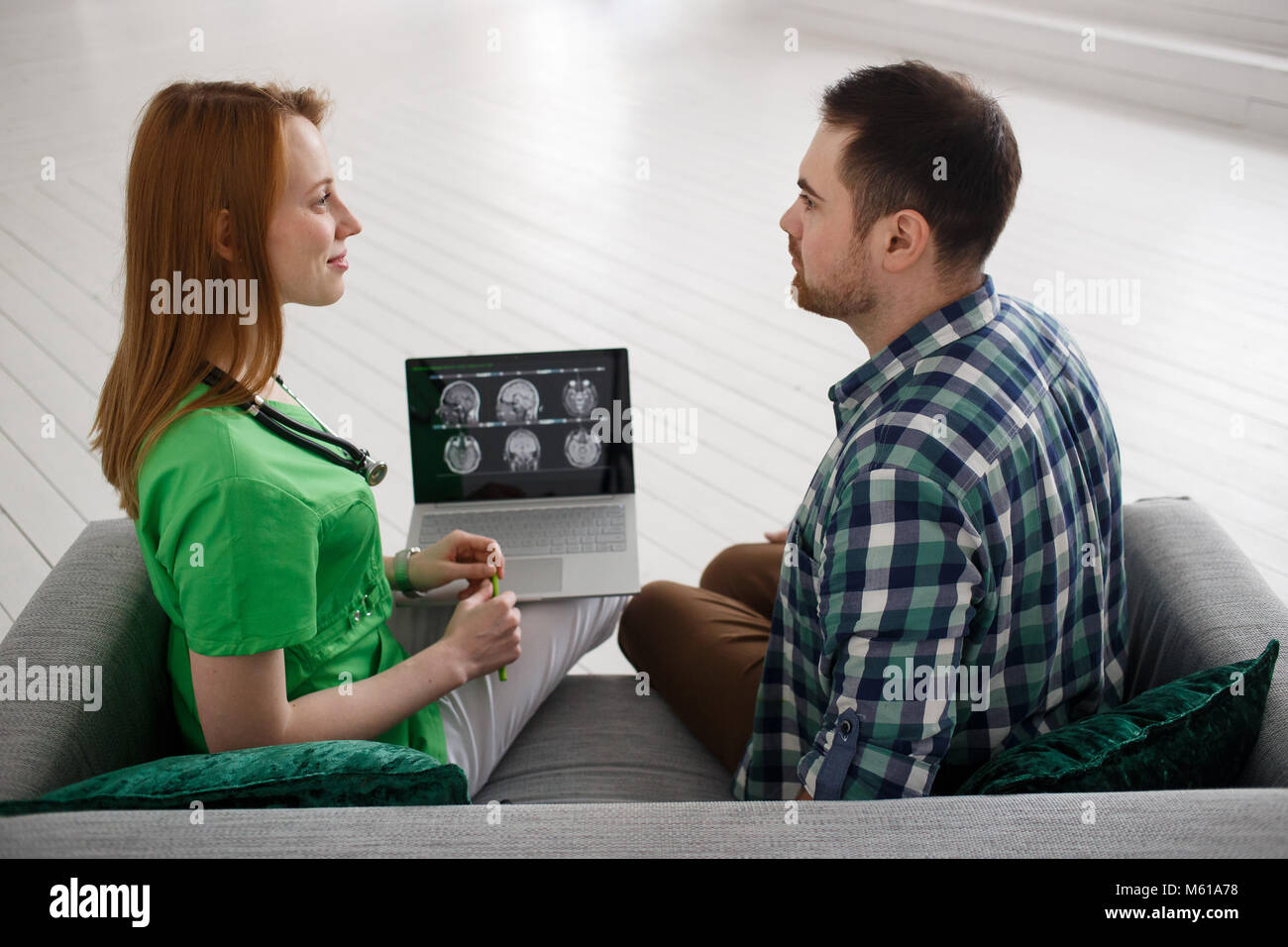 Female doctor and male patient looking at MRI concept healthcare, medical and radiology concept - Stock Image