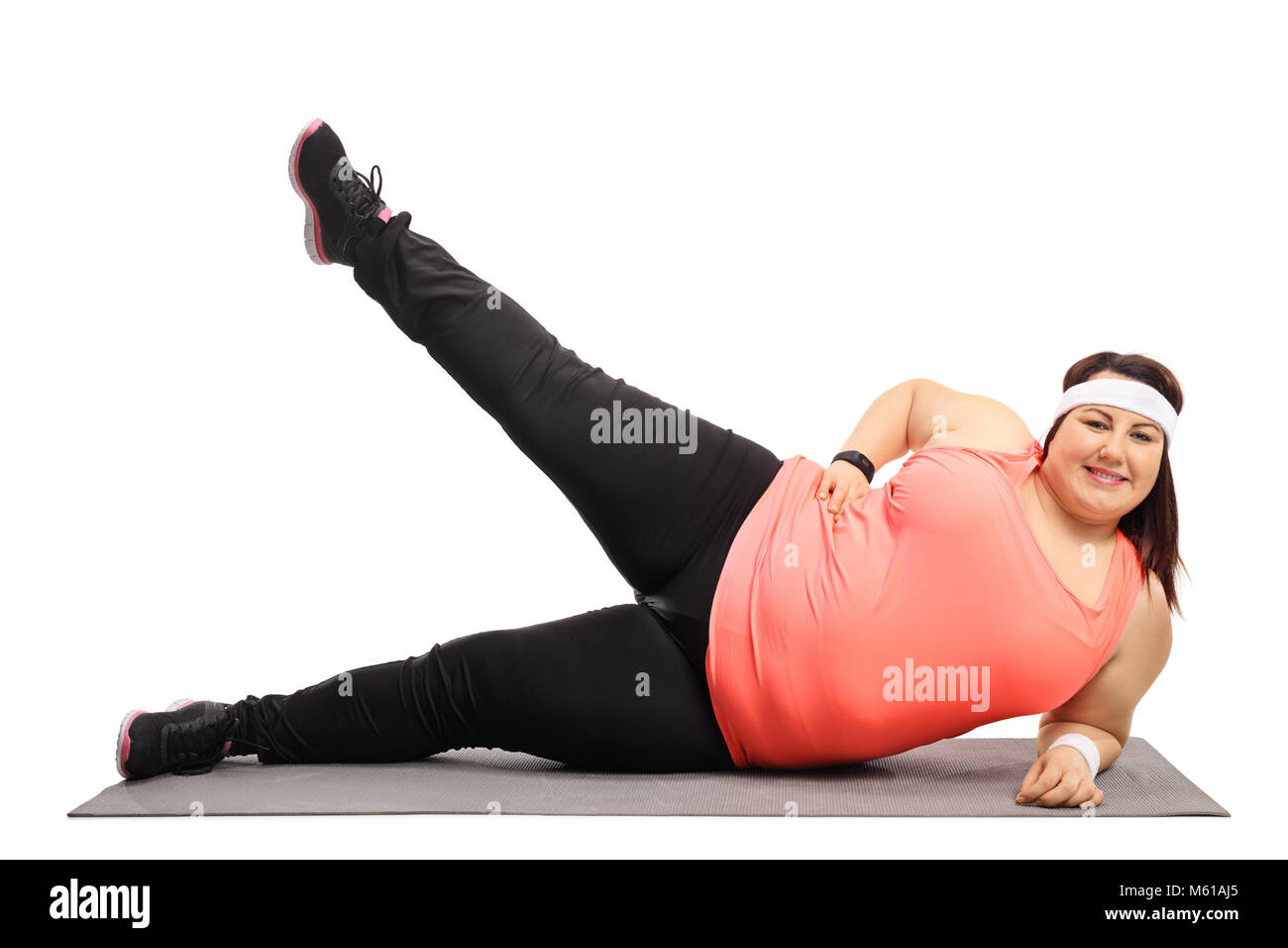 Overweight woman working out on an exercise mat isolated on white background - Stock Image