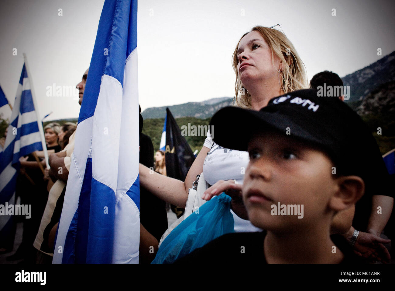 -  25/08/2012  -  Athens  -  A young boy wears Chryssi Avgi hat and listens carefully to the speaches with his mother - Stock Image