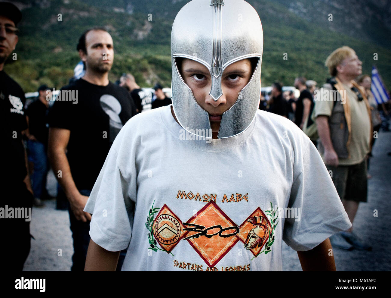Greece : Golden Dawn -  25/08/2012  -  Greece / Thermopylae  -  Child wears ancient greek helmet and t-shirt with - Stock Image