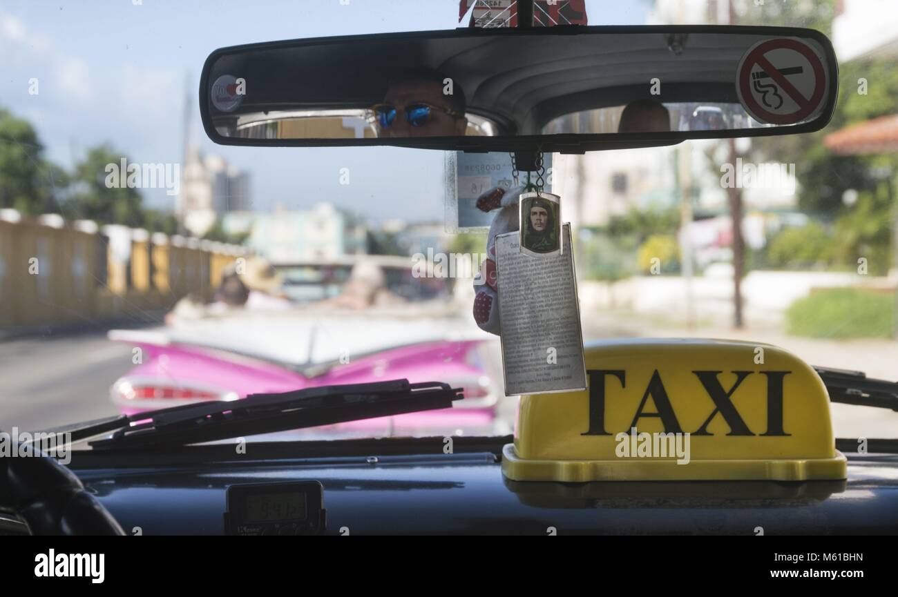 On the rearview mirror of a taxi in Havana hangs a small portrait of the Cuban revolutionary hero Che Guevara (1928 - Stock Image