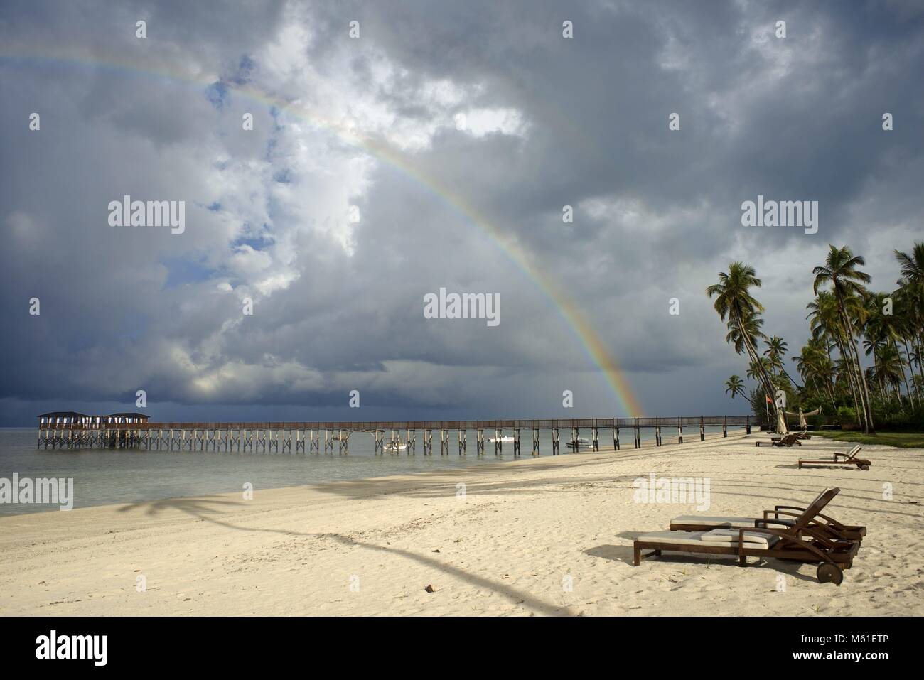 White sandy beach and hammocks below palm trees in front of The Residence Hotel at the Indian Ocean Zanzibar Tanzania - Stock Image