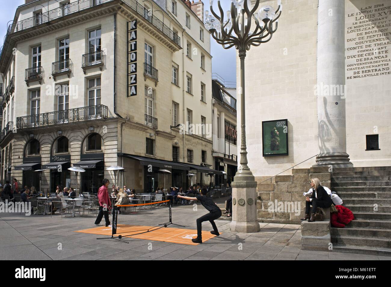 People Playing Mini Tennis In Front Of A Graslin Theater In The