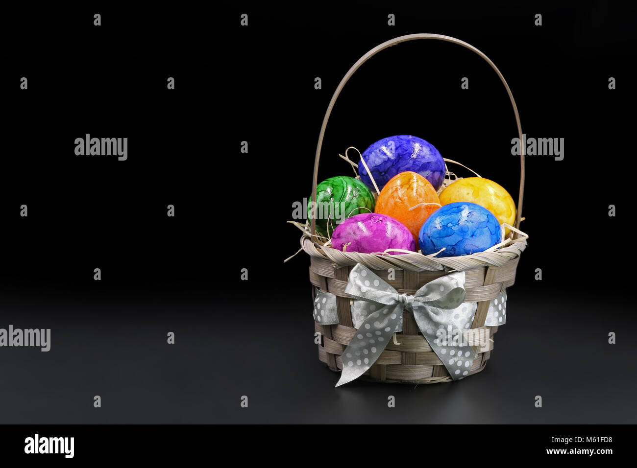colorful easter eggs in basket isolated on black background. - Stock Image