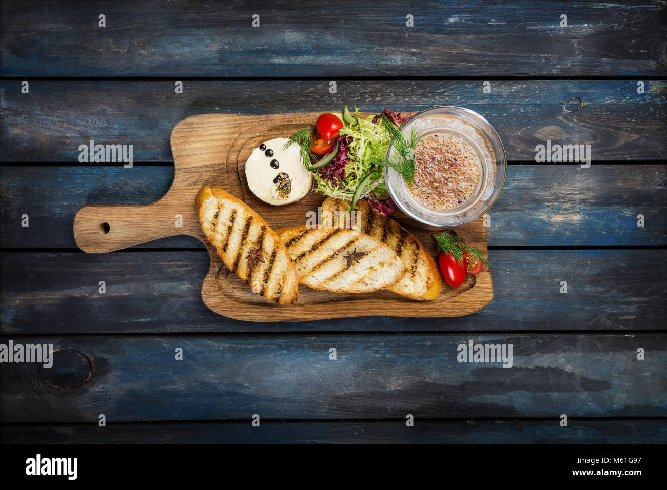 Toast with butter and caviar on a wooden background - Stock Image