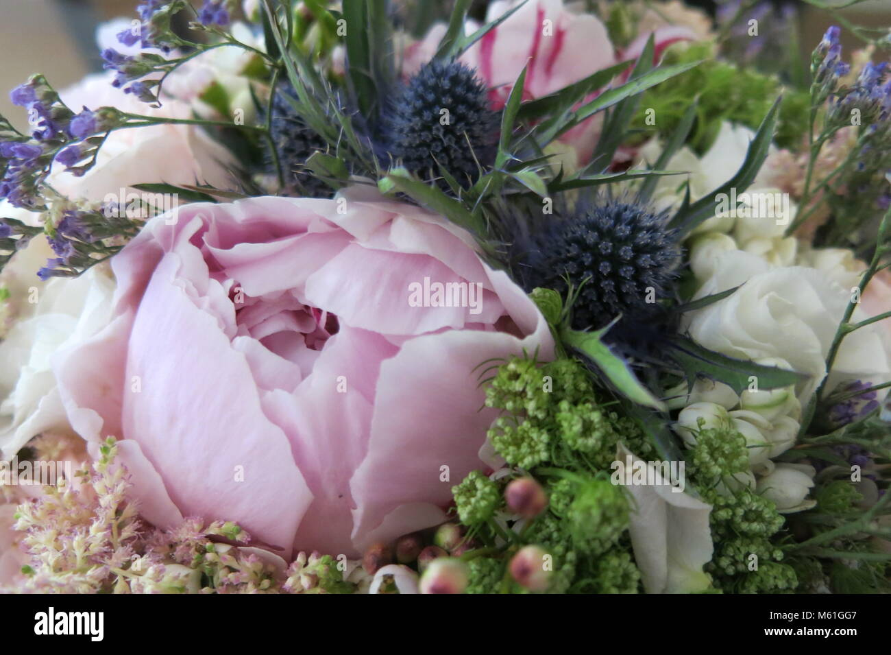 A blowsy, romantic bridal bouquet in pink, white and blue Stock Photo