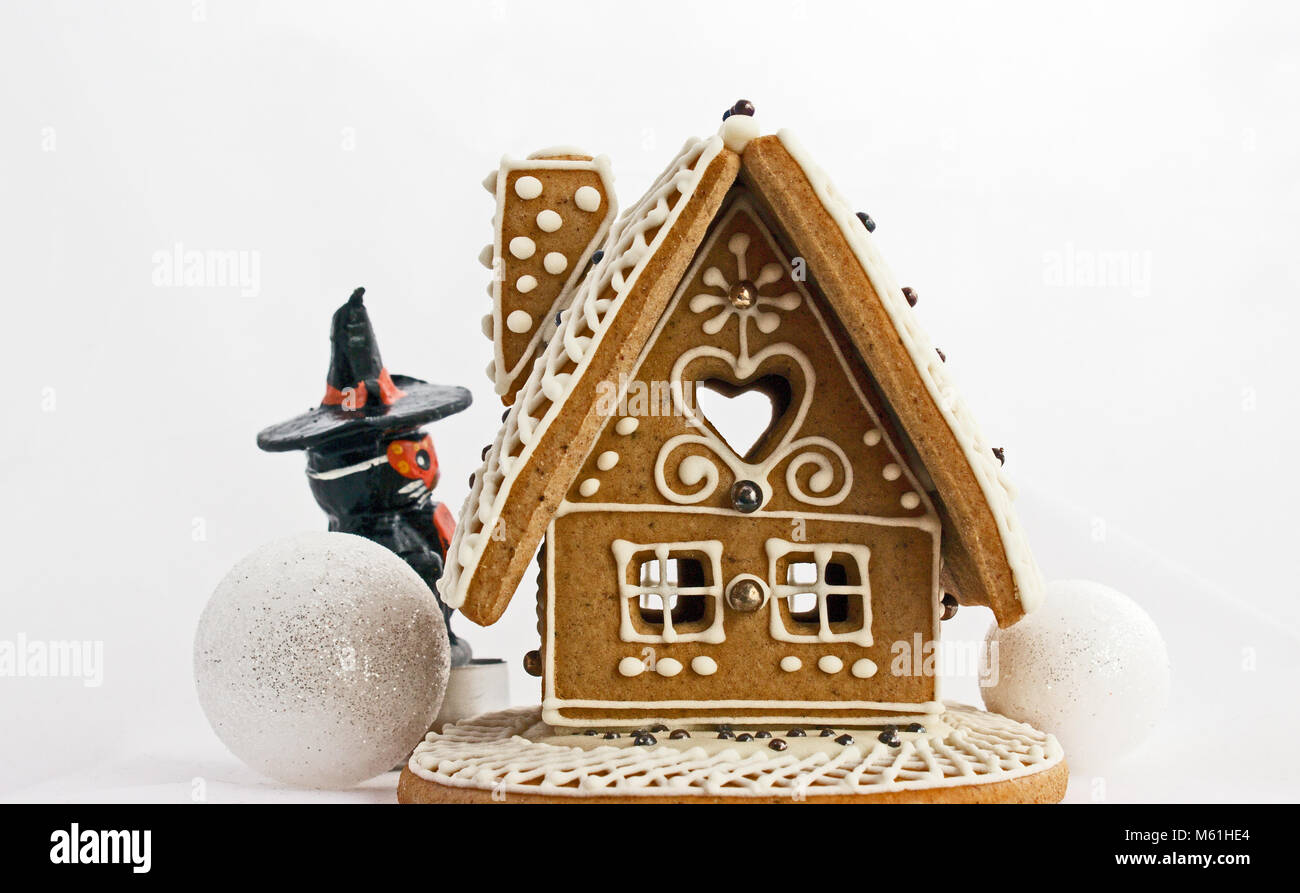 The gingerbread house with two snowball and magician. The white sky in the background. Stock Photo