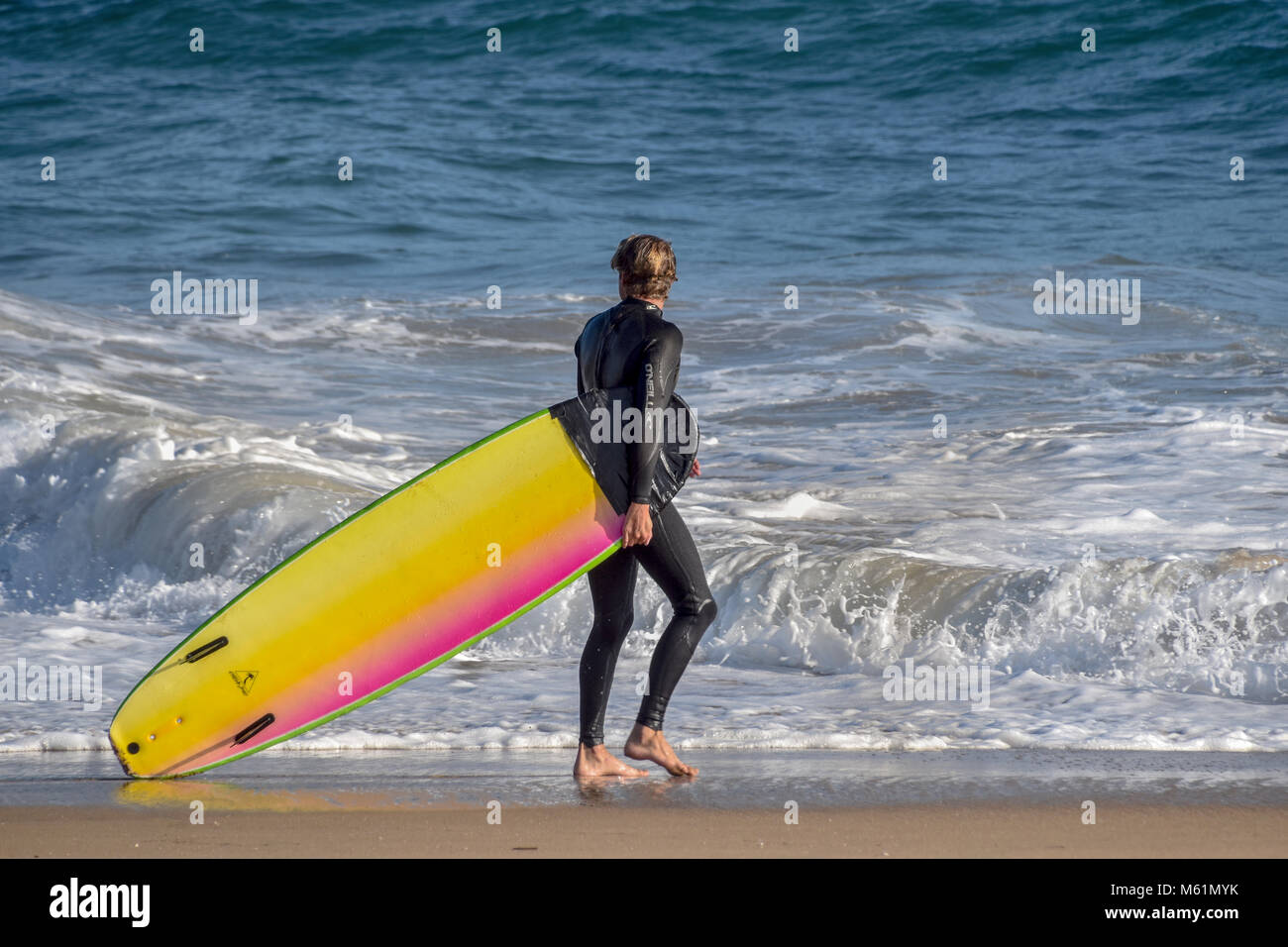 A surfer walks along Huntington City Beach checking out the waves. Huntington Beach is known for it's surfing - Stock Image