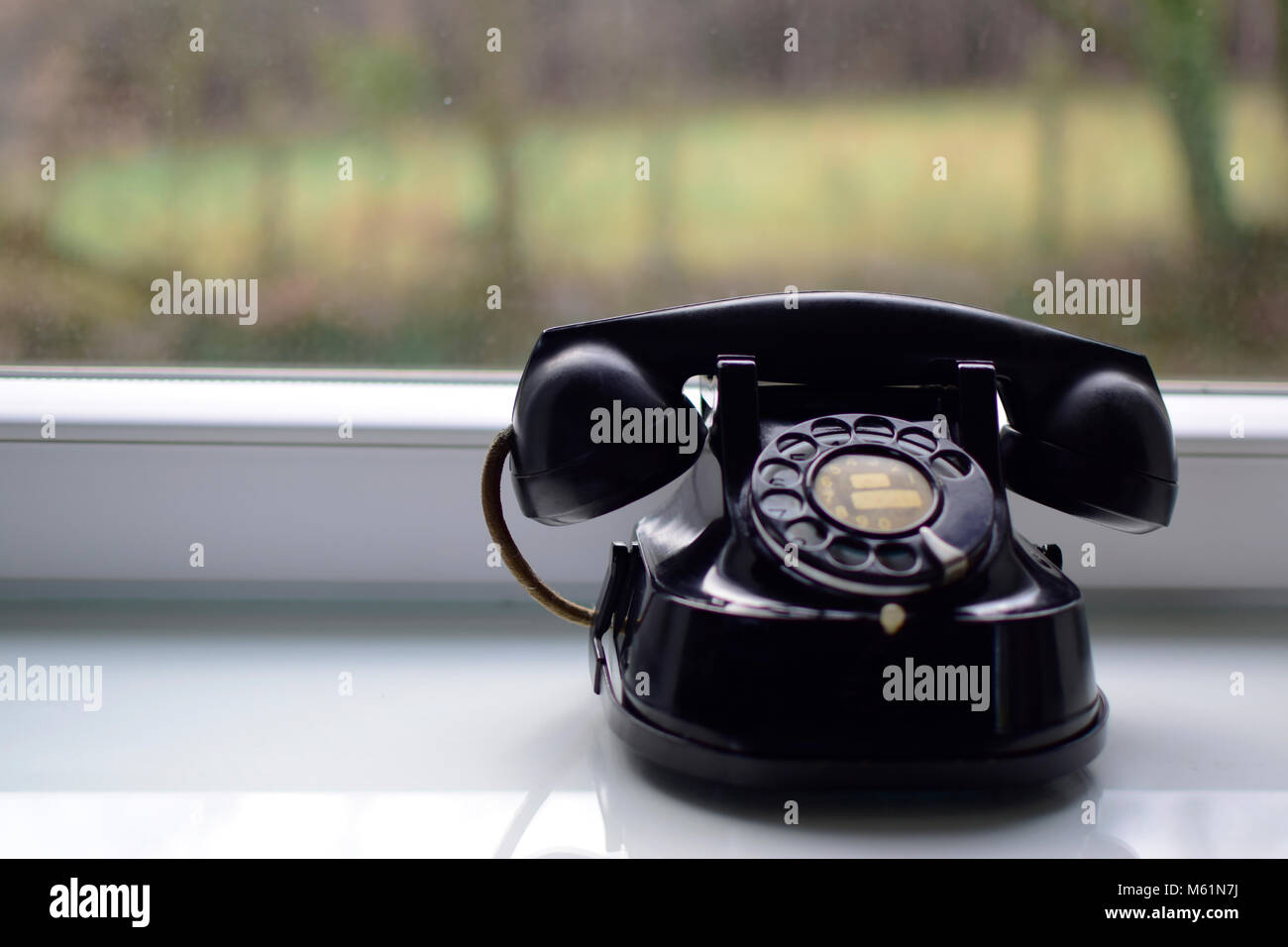 Vintage black telephone on the table near window with blurred background. - Stock Image