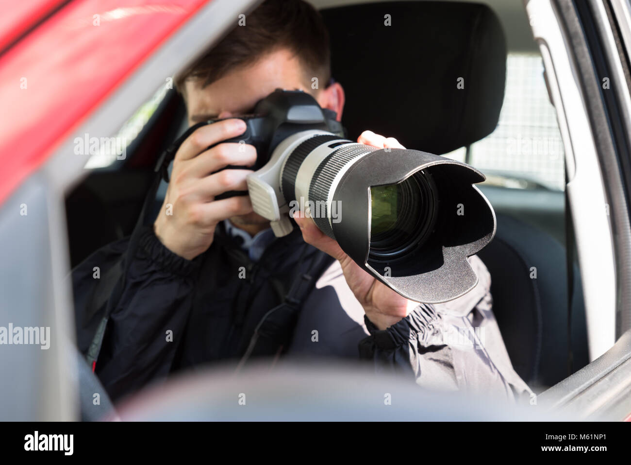 Side View Of A Private Detective Sitting Inside Car Photographing With Slr Camera - Stock Image