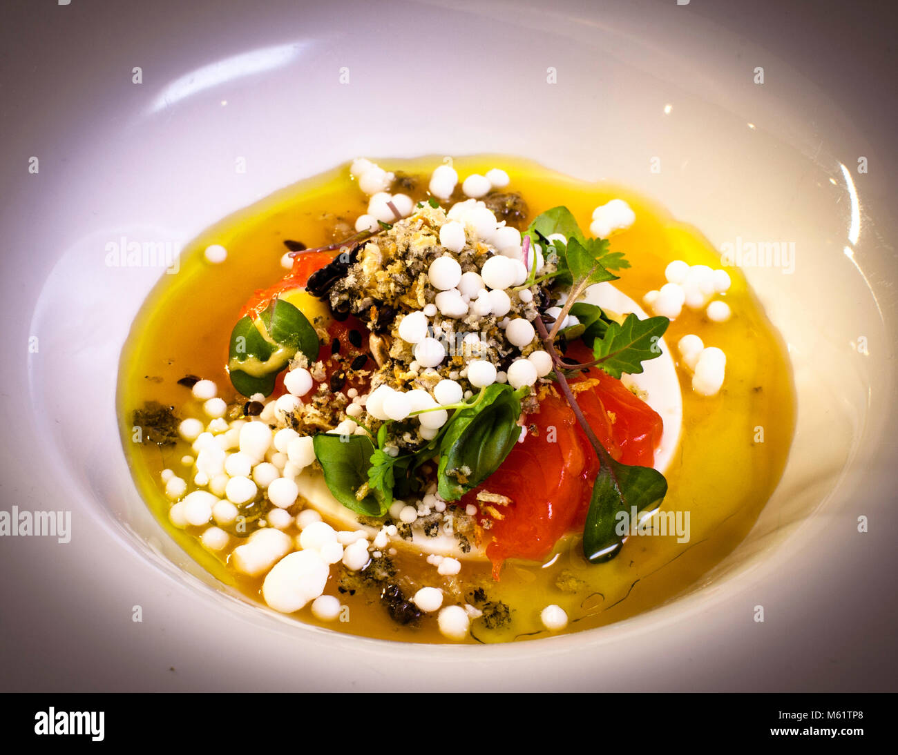 Cooked cow's milk with trout and tomato tea by Michelin Star Chef Marco Müller Stock Photo