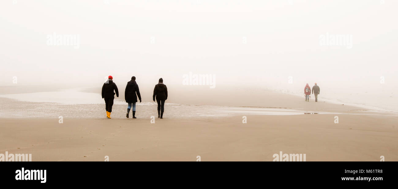 3 people walking, misty beach,  seaside resort, St. Peter Ording, Germany. In tideways, the water flows to the sea at low tide and in the other direction at high tide. In fog, the Wadden Sea can become a labyrinth Stock Photo
