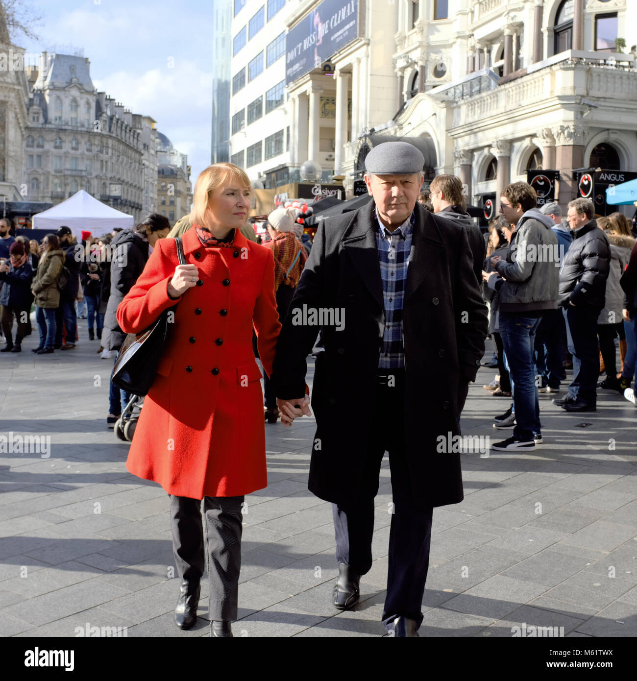 Older man holding hands with younger woman in Leicester square, London, England, UK - Stock Image